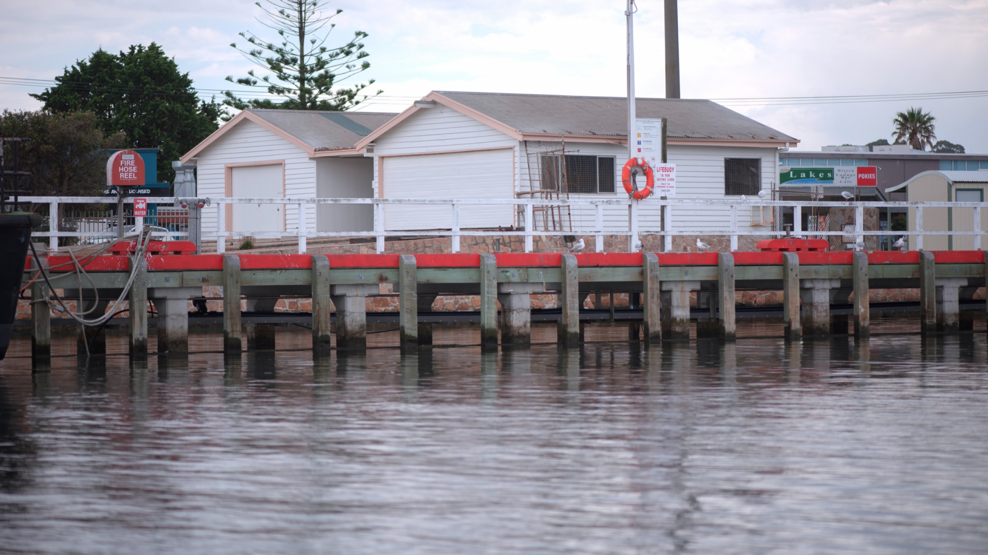 Photo two white weatherboard, pitched roof structures on small jetty with red stripe above lake water